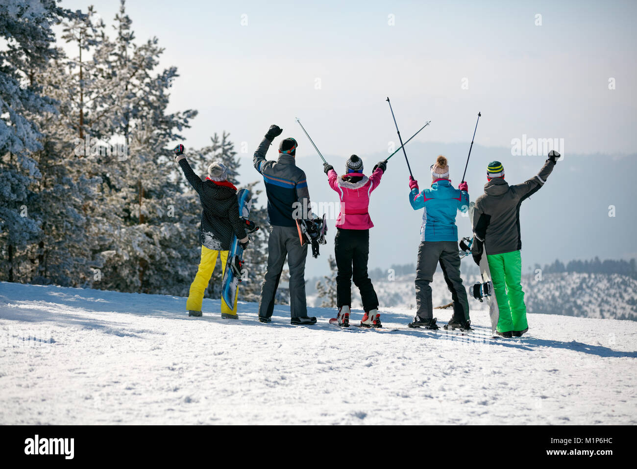 Happy skiing group on the mountain top on sunny day. Back view - Stock Image