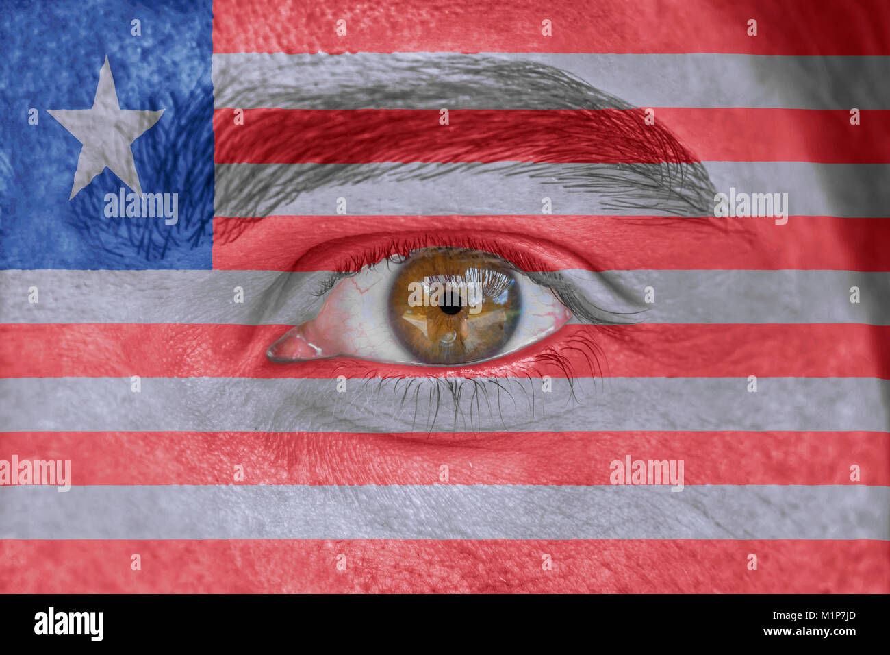 Human face and eye painted with flag of Liberia - Stock Image