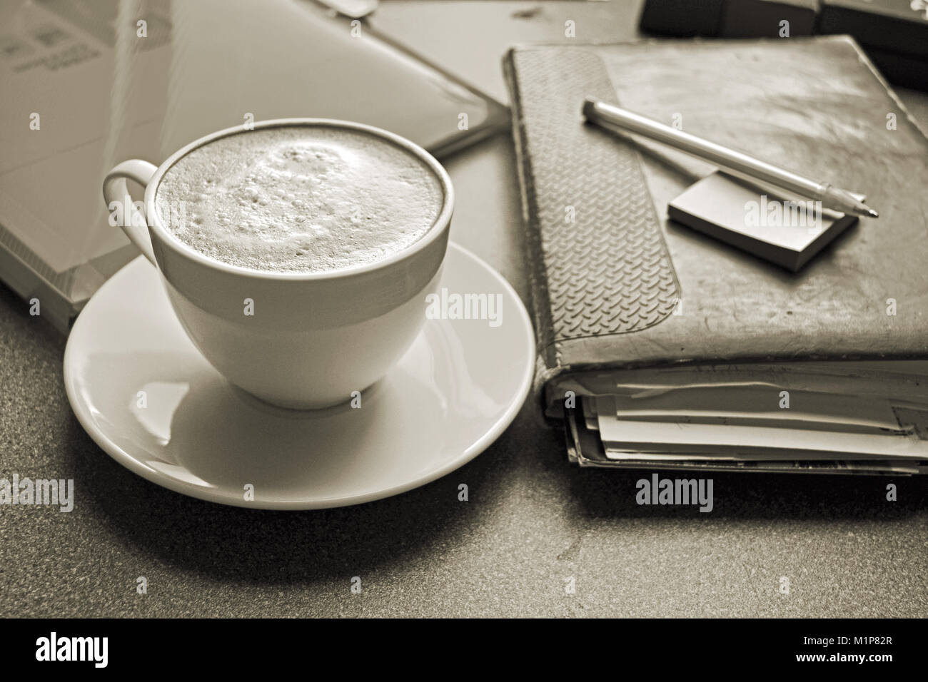 A cup of freshly brewed coffee on a desk with a diary and pen, treated in sepia - Stock Image