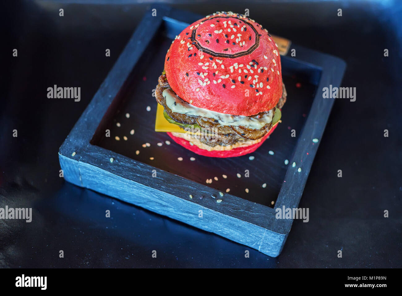 Red burger on a wooden board - Stock Image