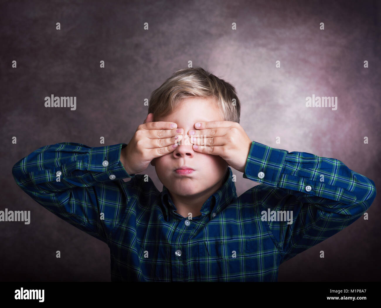 Boy with closed eyes on a dark background - Stock Image