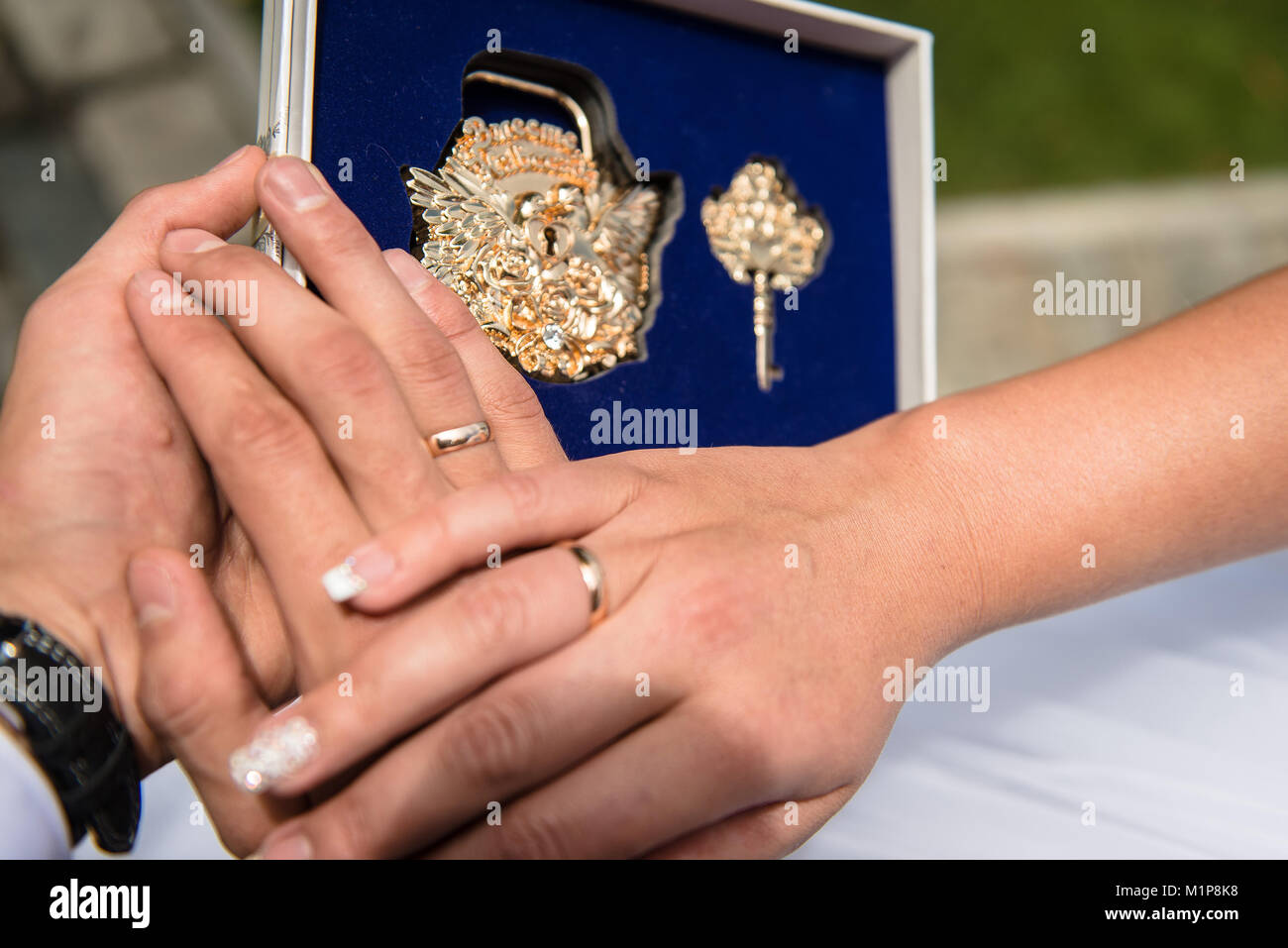 Close up hands of newlywed and wedding lock - Stock Image