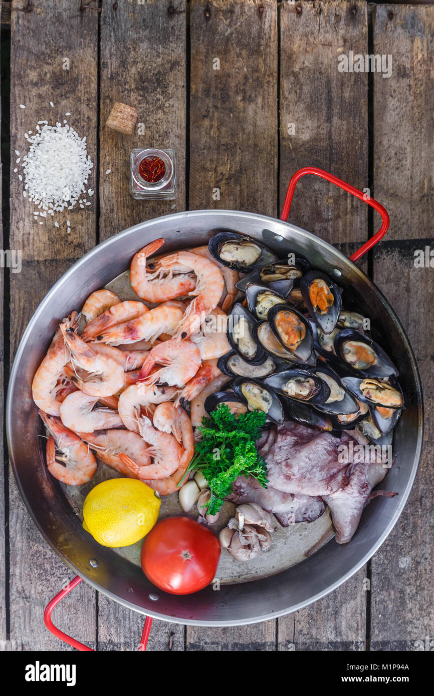 Raw seafood products in paella pan on a wooden table, top view - Stock Image