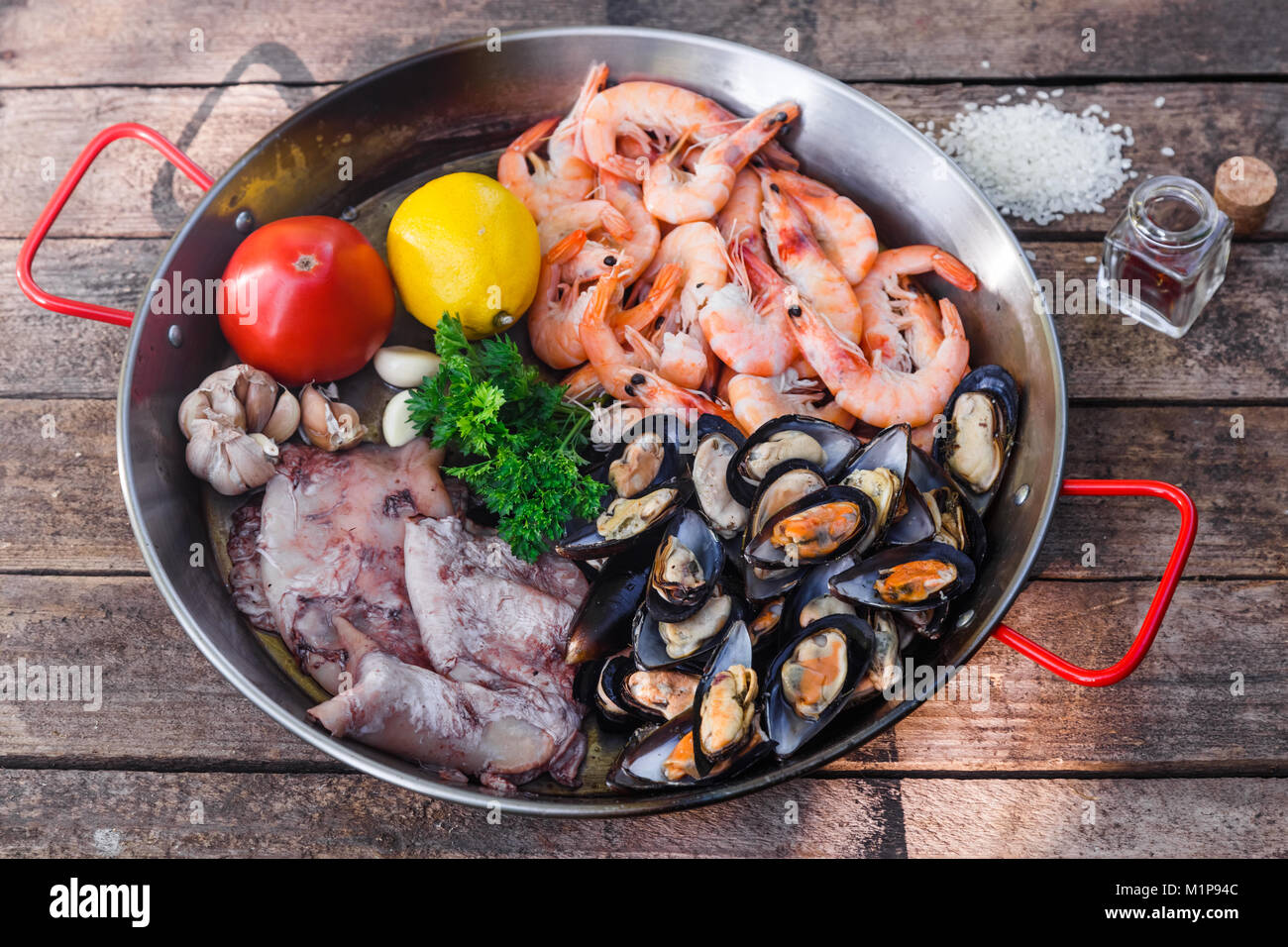 Raw seafood products in paella pan on a wooden table - Stock Image