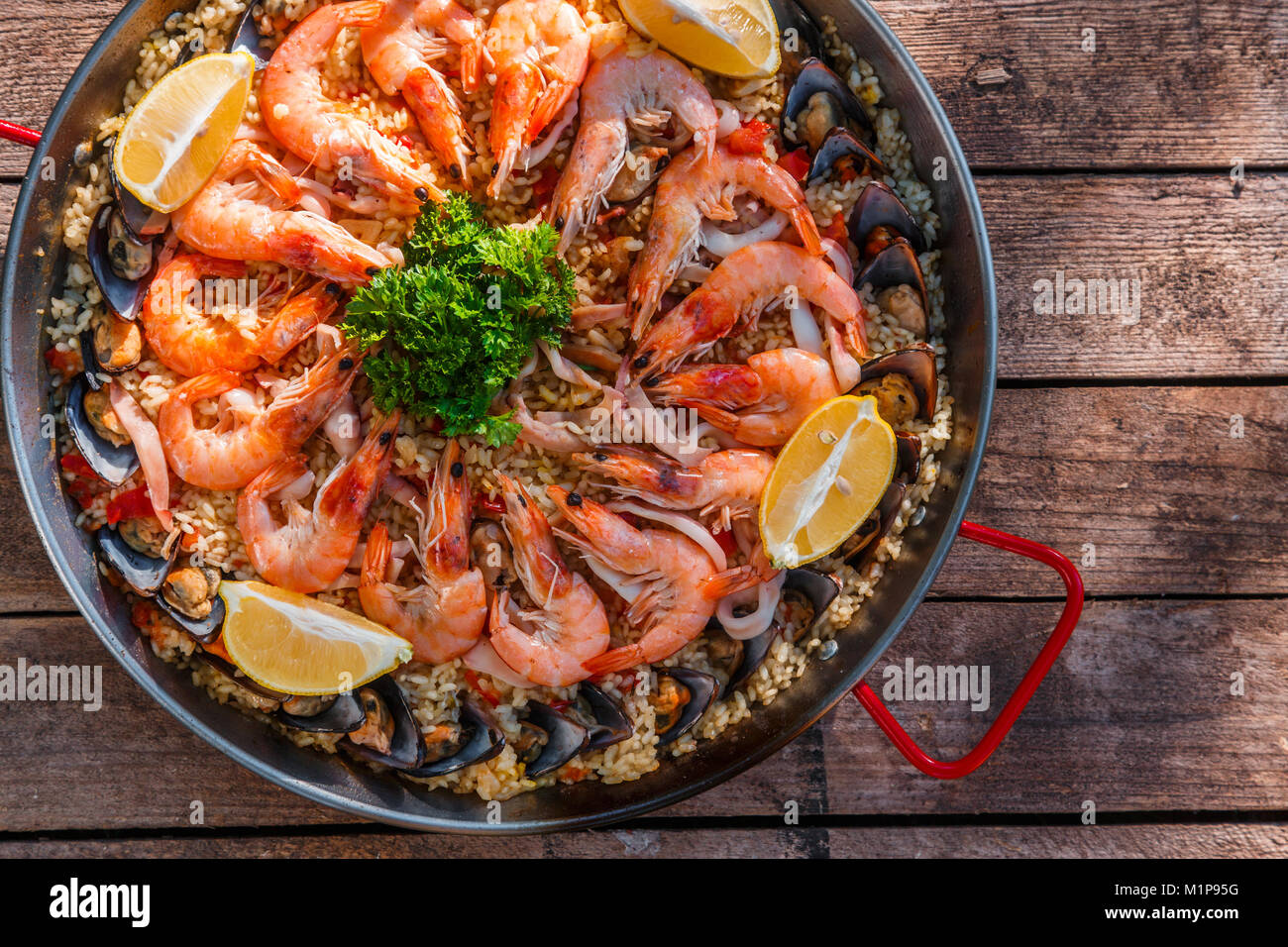 Traditional seafood paella in the fry pan on a wooden old table, top view - Stock Image