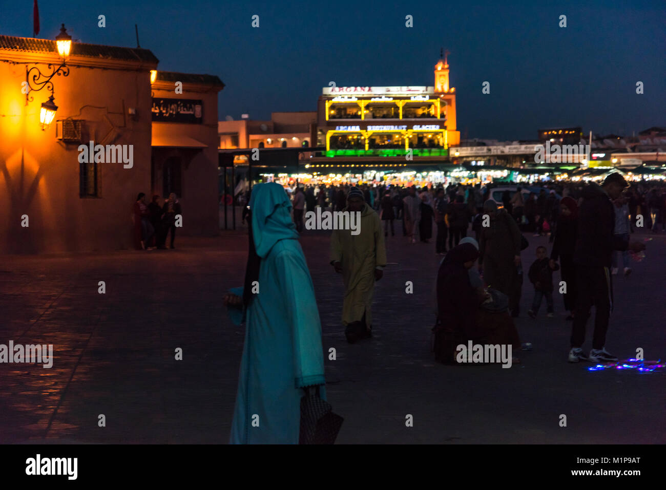 Marrakech,Morocco - January 2018: Muslim woman walk by in  Jamaa el Fna market square at evening. Stock Photo