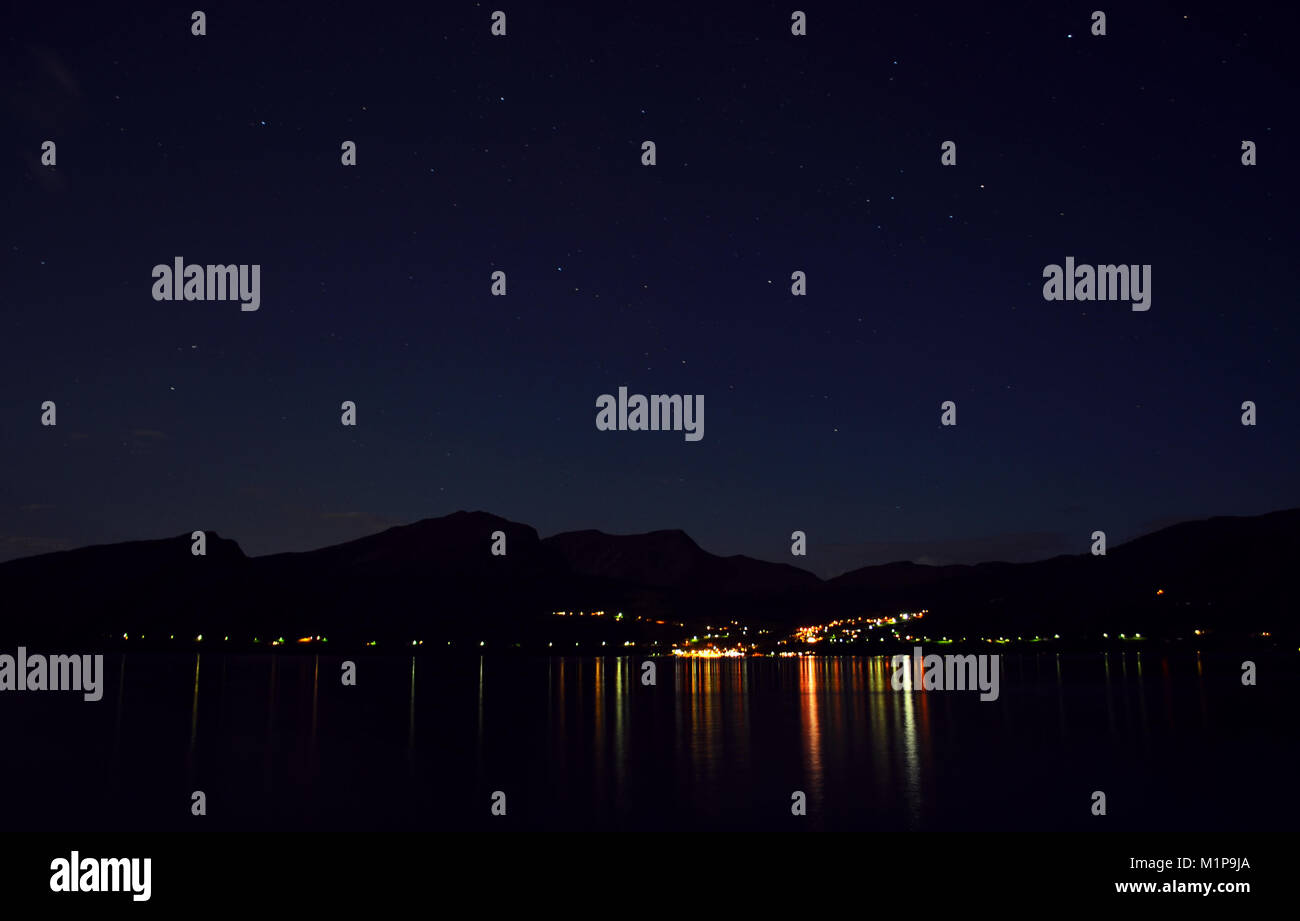 Night shot of harbor at the mountains and Fjords in Norway, Volda. Reflections in the water. City lights, romance, - Stock Image