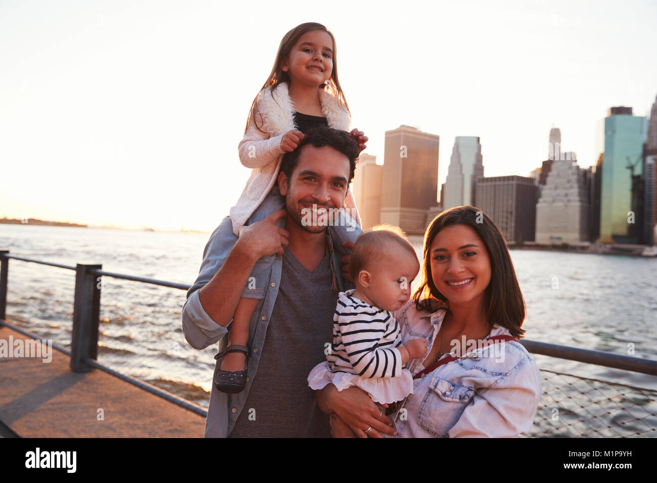 Young family with daughters standing on quayside, close up - Stock Image