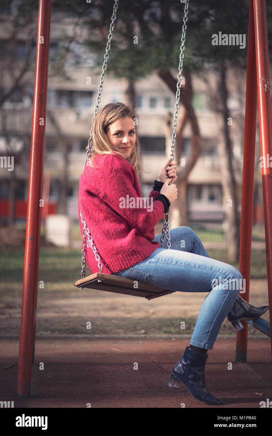 Reliving childhood, swinging in a park - Stock Image