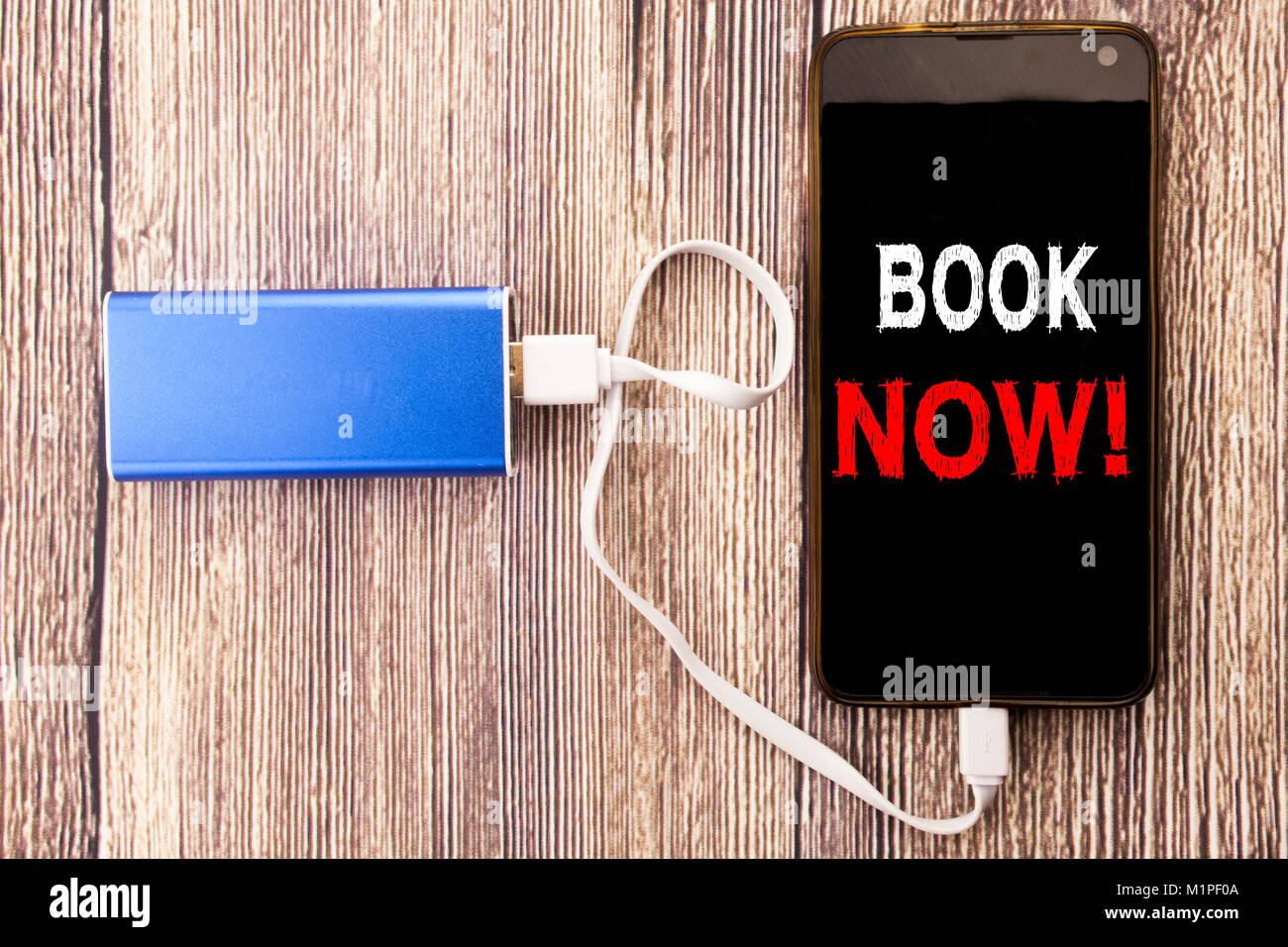 Word, writing Book Now. Business concept for Reservation Booking written on mobile phone mobile and power-bank charger - Stock Image