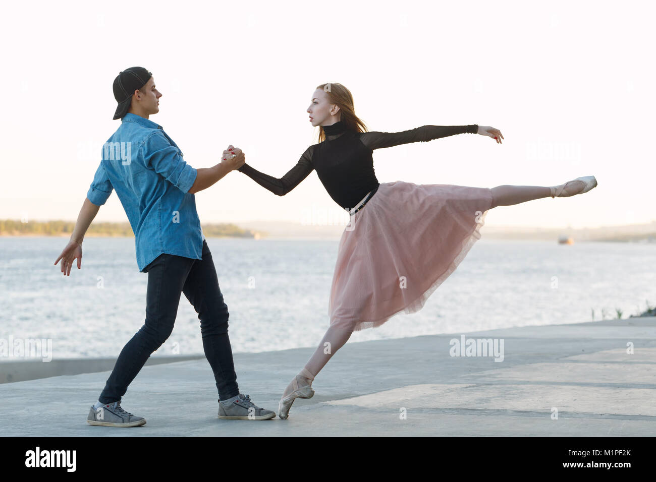 Slender ballerina dances with a modern dancer. Dating lovers. Passion and romance of dance. He holds her hand. Performance - Stock Image