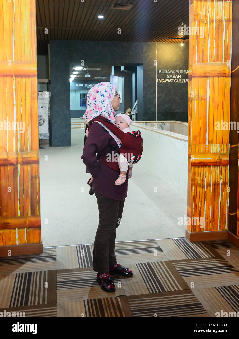 Malaysian mother carrying her sleeping baby at the Muzium Sabah, Kota Kinabalu, Sabah, Borneo, Malaysia - Stock Image