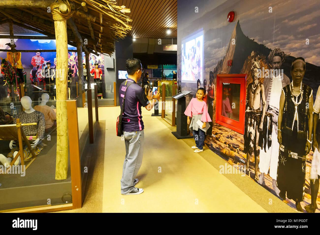 Father taking a picture of his daughter at the Muzium Sabah, Kota Kinabalu, Sabah, Borneo, Malaysia - Stock Image