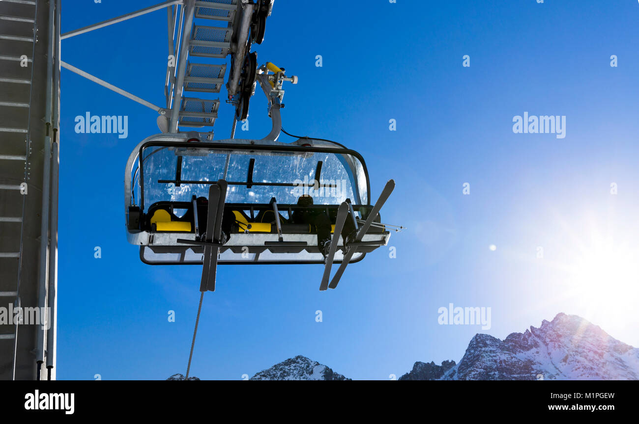 Skiers going up on the chairlift against bright blue sky- ski resort in Italy on sunny winter day - Stock Image