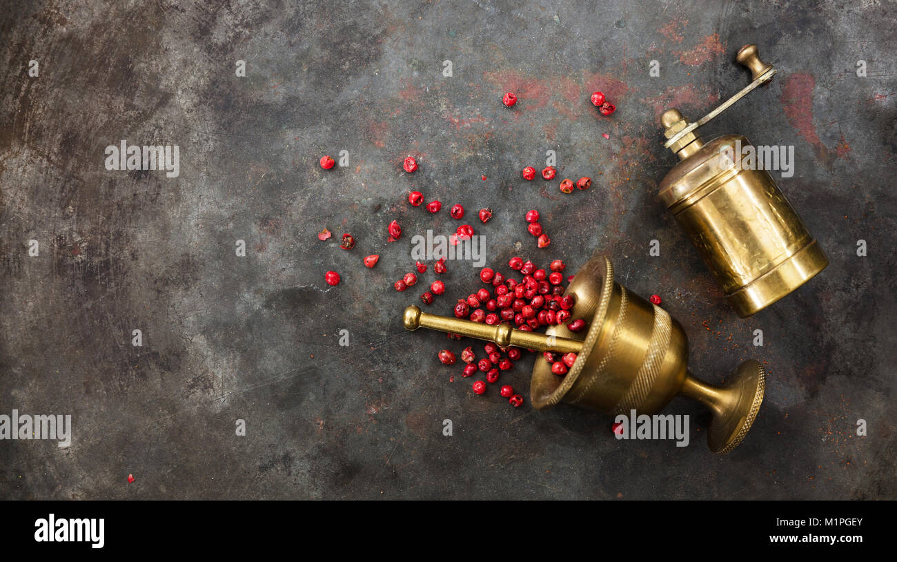 Pink pepper seeds, a brass pepper mill and a mortar on metal rusty background, top view, copy space - Stock Image