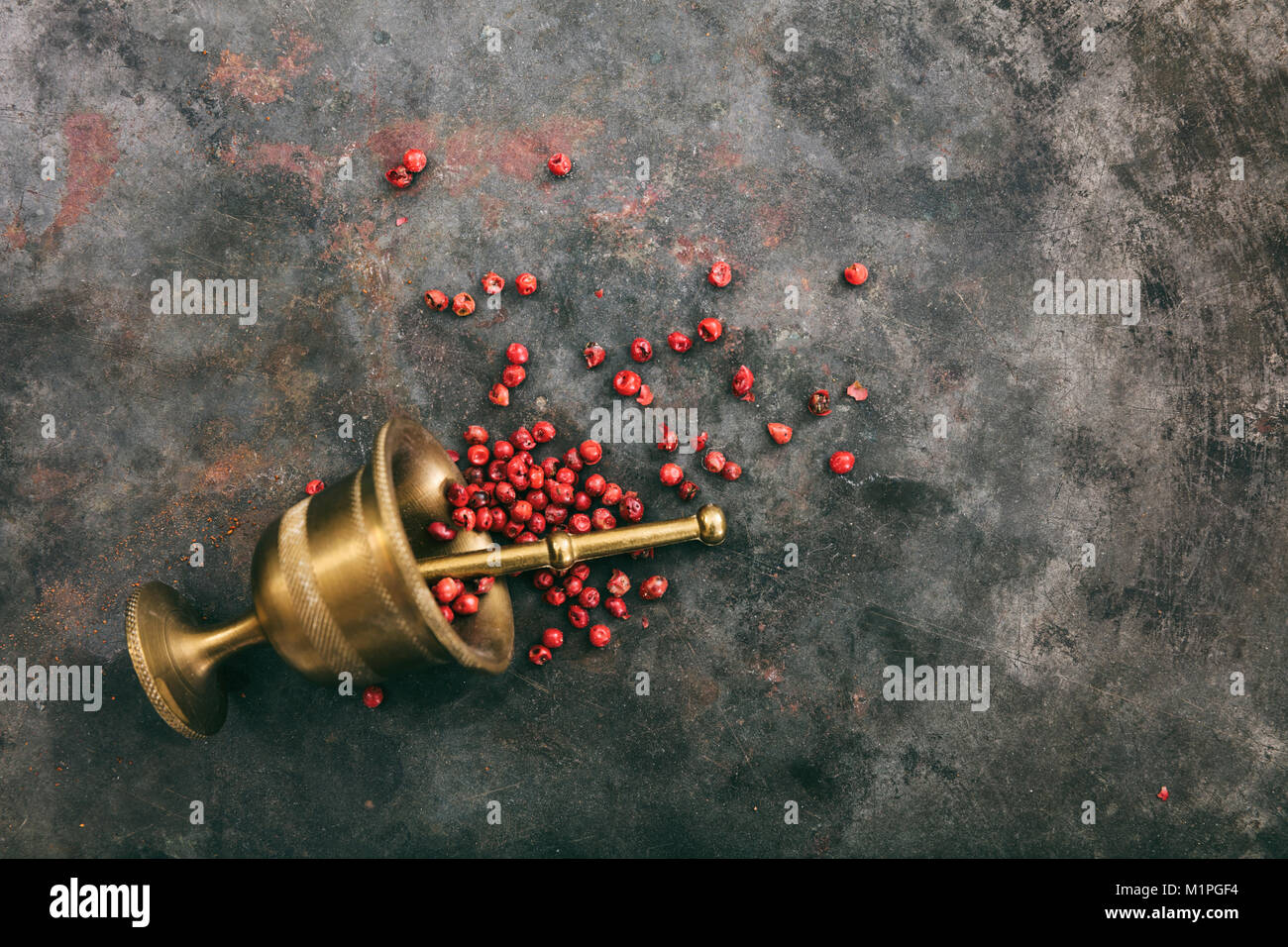 Pink pepper seeds and a brass mortar on metal rusty background, top view, copy space Stock Photo