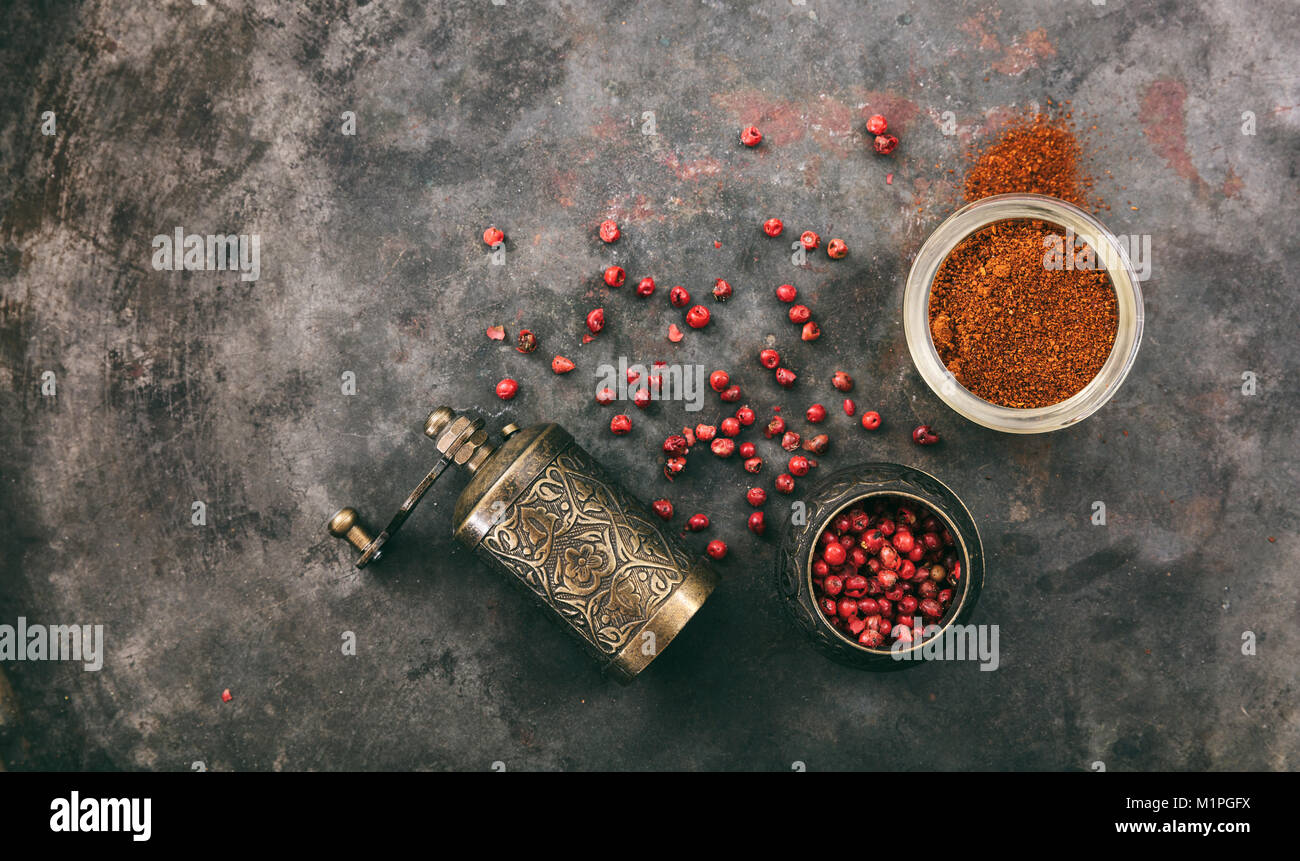 Pink pepper seeds and powder and a brass pepper mill on metal rusty background, top view, copy space - Stock Image