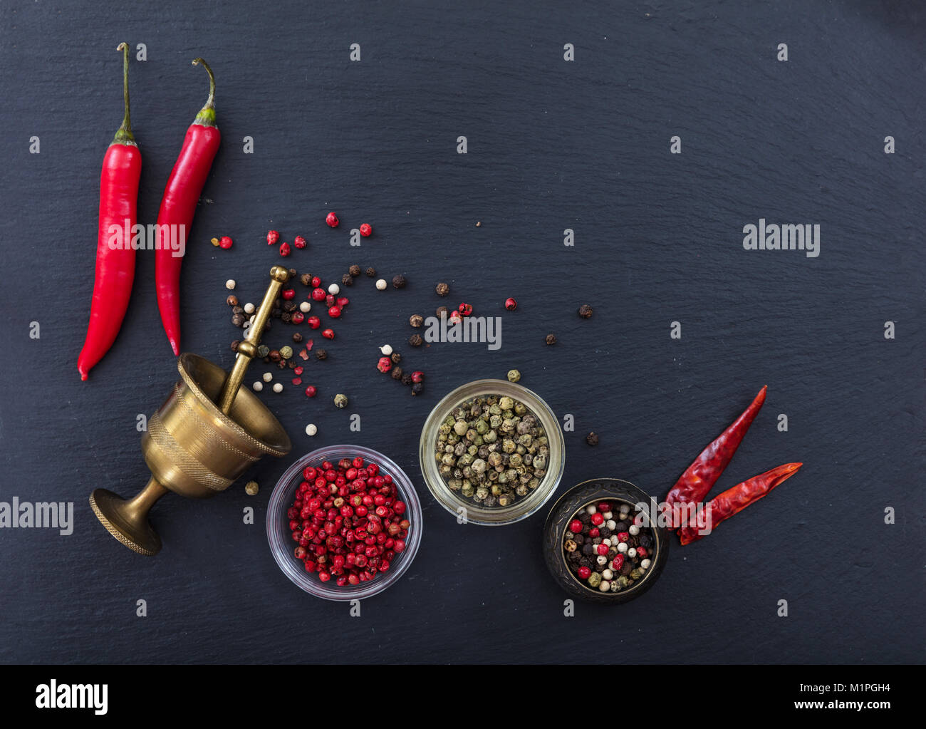 Various peppercorns and peppers and a brass pepper mill on black stone background, top view, copy space - Stock Image