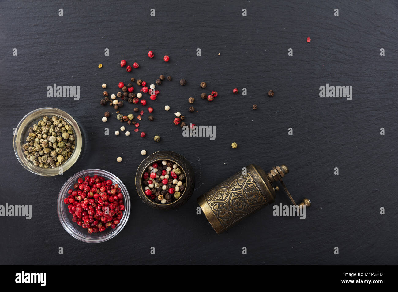 Various pepper seeds and a brass pepper mill on black stone background, top view, copy space - Stock Image
