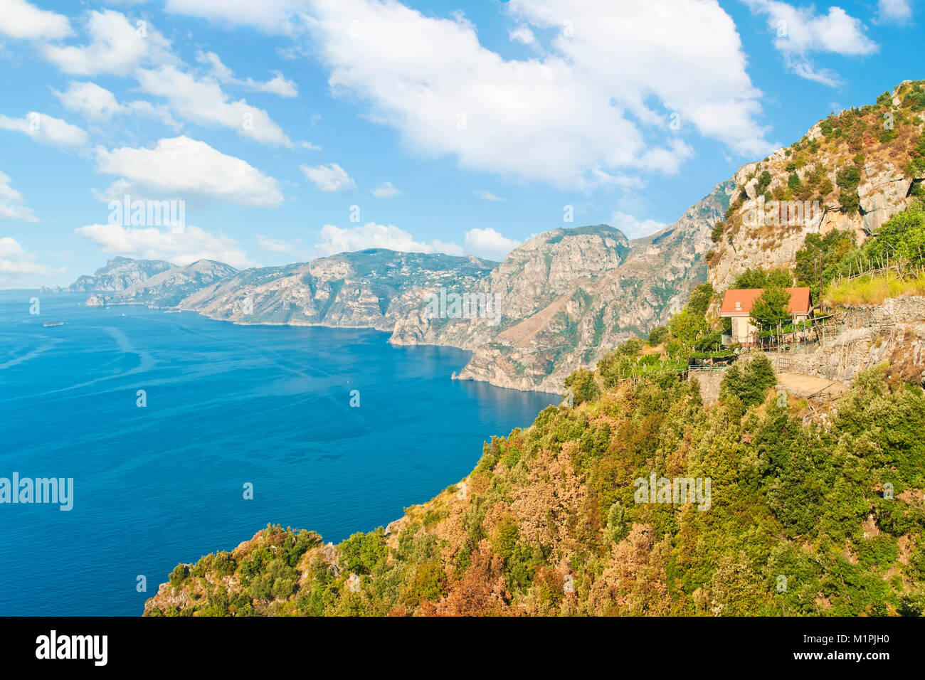 view of small country house on edge of cliff with mountain range at background on Path of Gods hiking track along - Stock Image