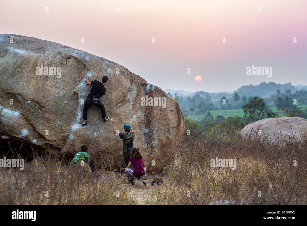 A group of people bouldering in Hampi,India at sunset. - Stock Image