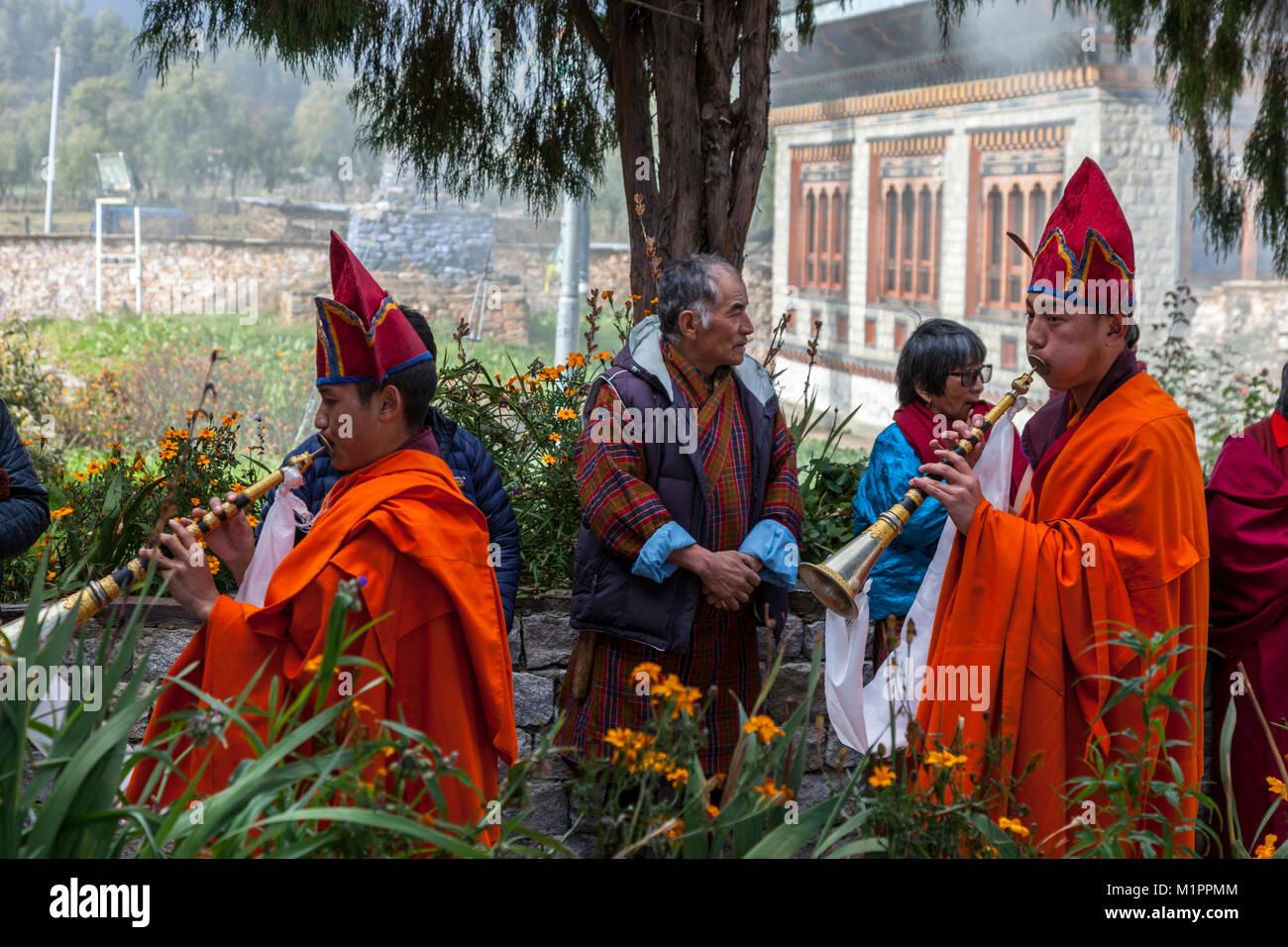 Bumthang, Bhutan.  Monks Playing Trumpets Entering Jambay Lhakhang Monastery. - Stock Image
