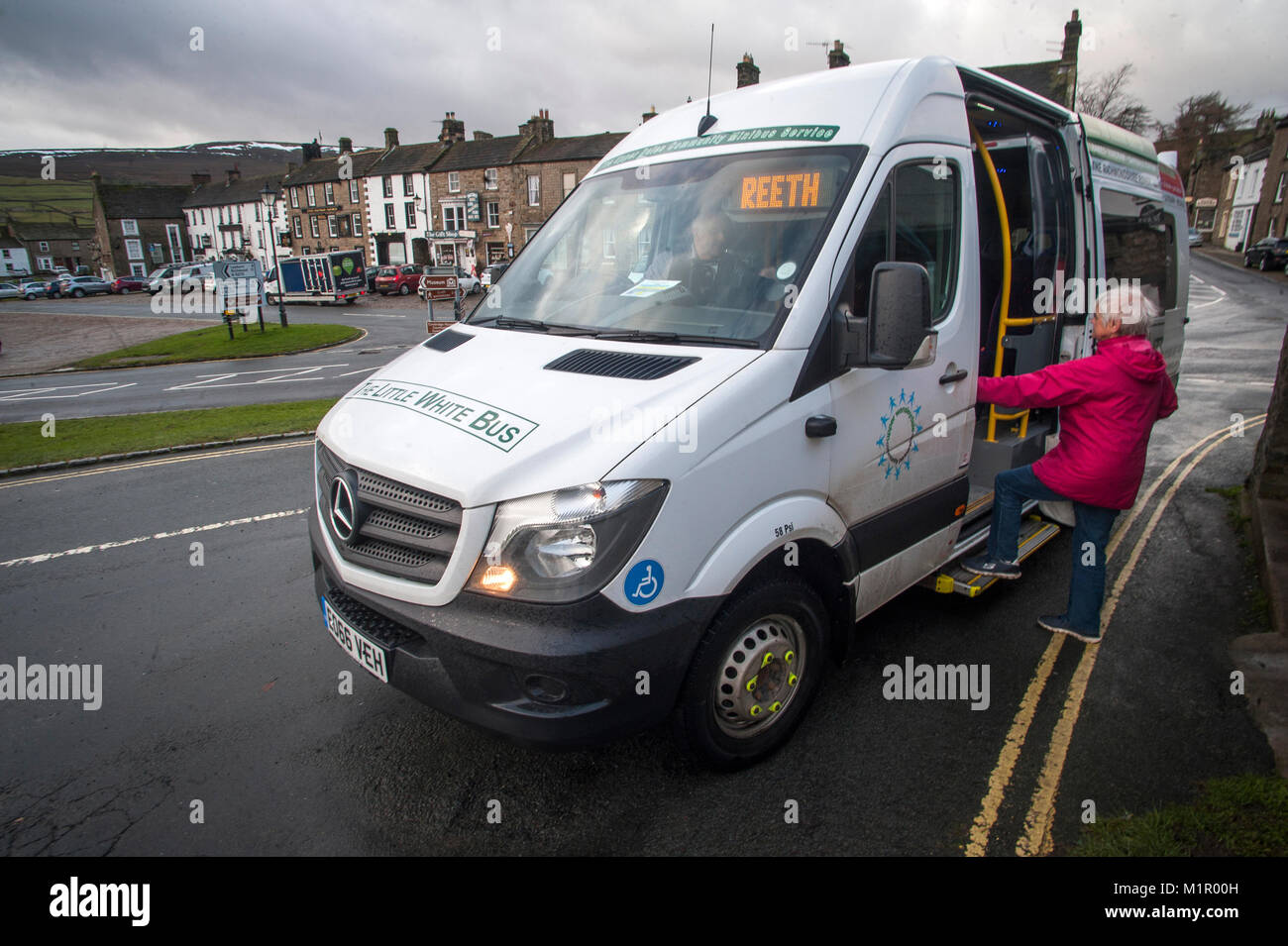 76 yr old Ruth Emerson boards the Little White Bus at Reeth in upper Swaledale to travel to Richmond. Stock Photo