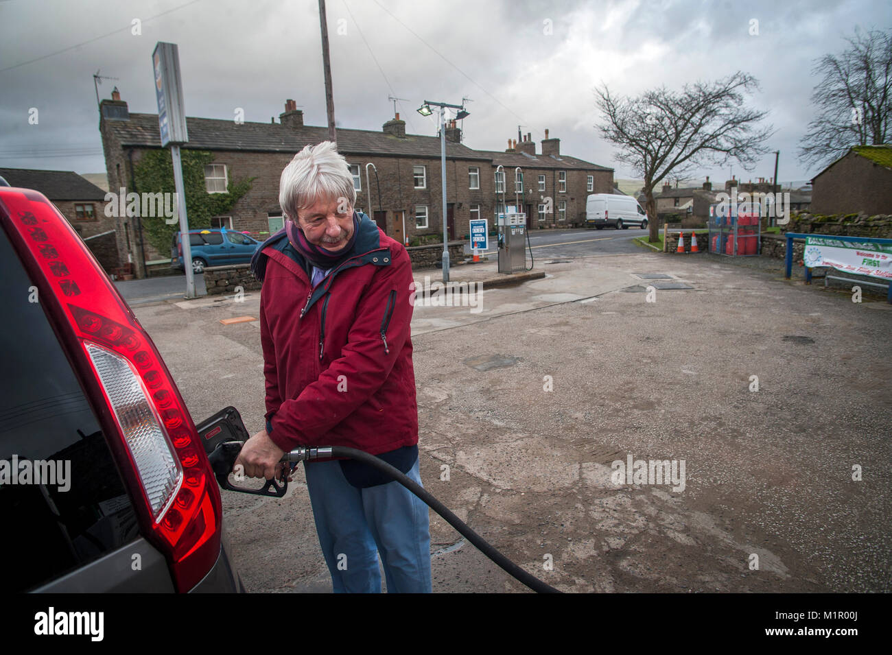 John Blackie Filling up at the Dale Head Petrol Station now run by the local community in Hawes. The first community - Stock Image