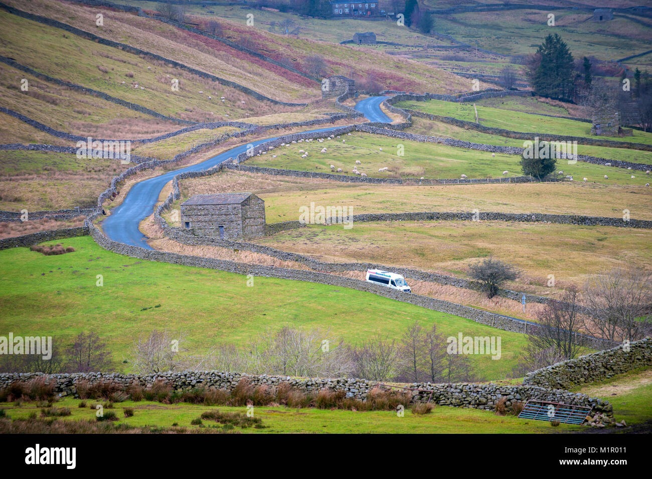 The Little White Bus makes its way on its Swaledale shuttle route this time leaving Keld for next stop Muker. - Stock Image