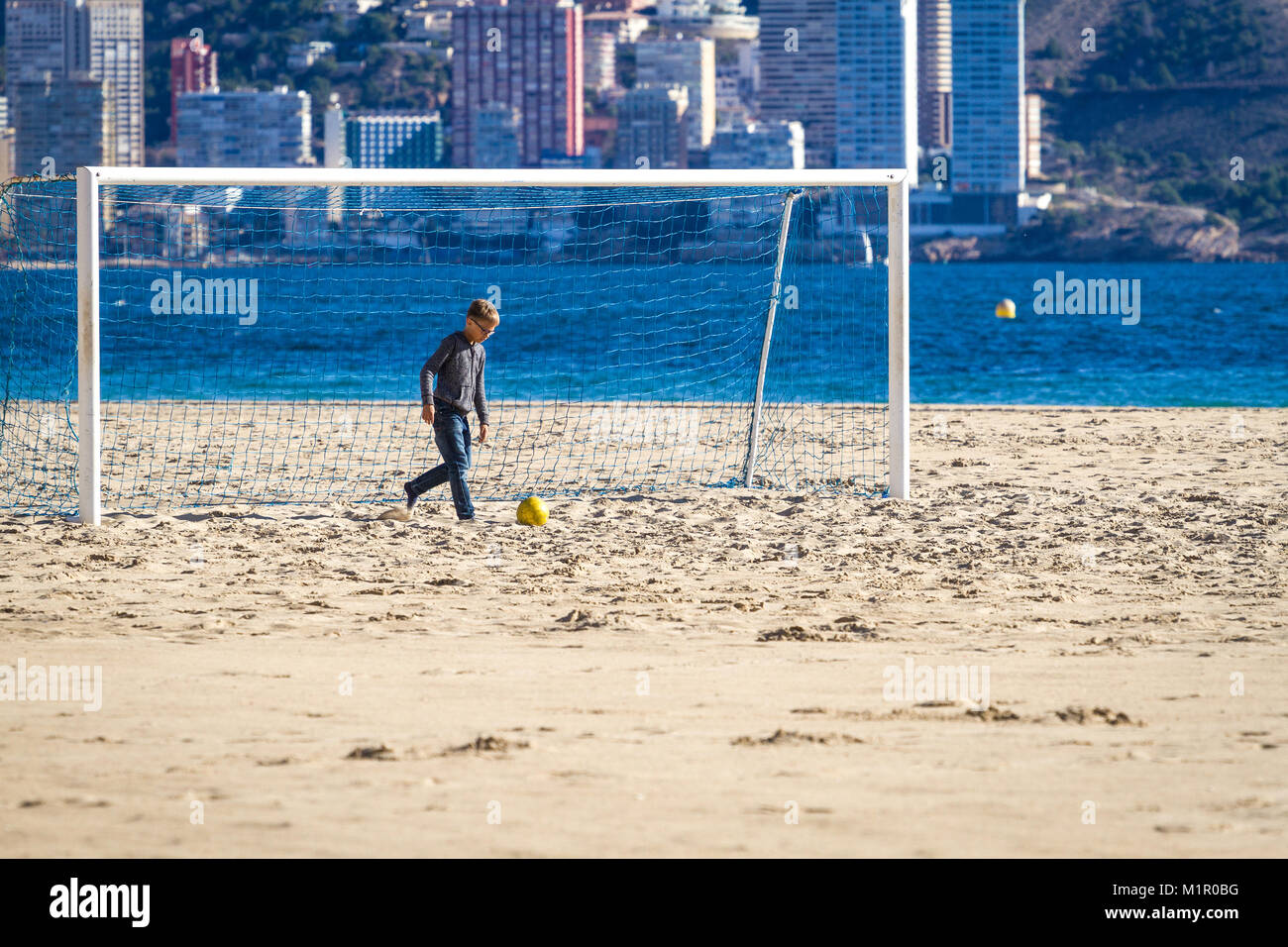 Boy playing football on the beach - Stock Image