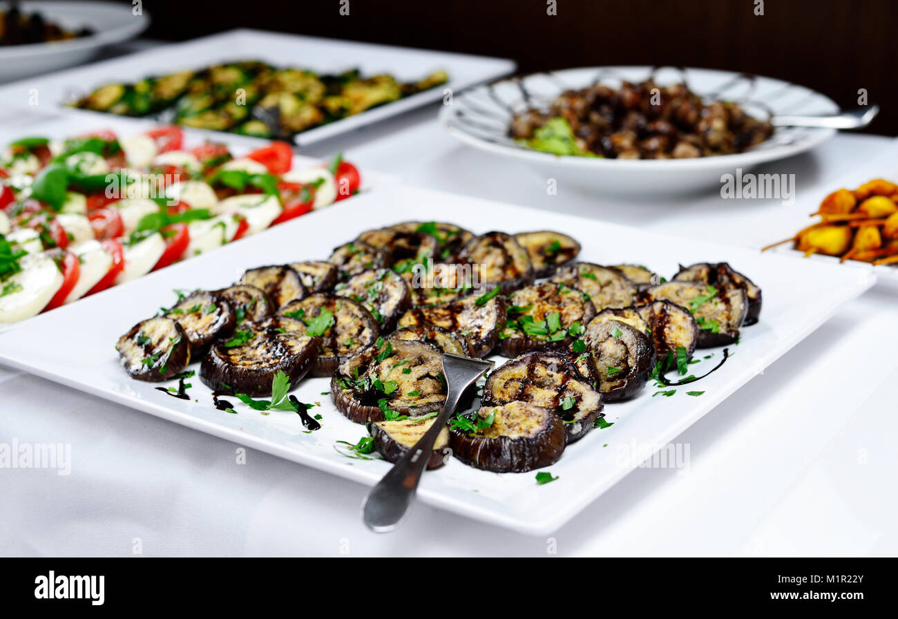 Party buffet or banquet scene with italian antipasti. Grilled eggplant vegetable, tomato and mozzarella and various - Stock Image