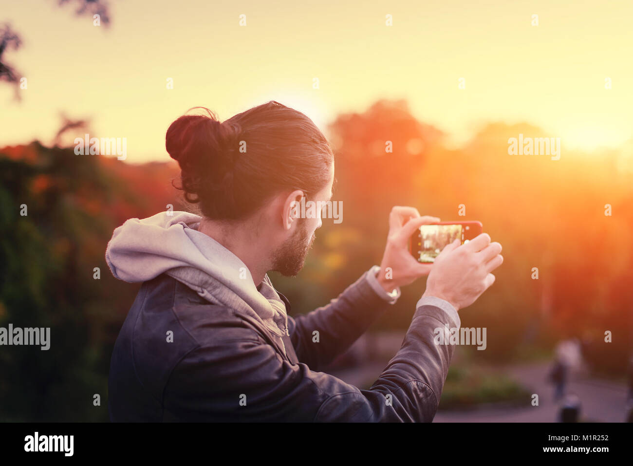 The guy makes a photo of the sunset on the phone. Tourist with phone. Photos and low keys and with a soft focus. - Stock Image