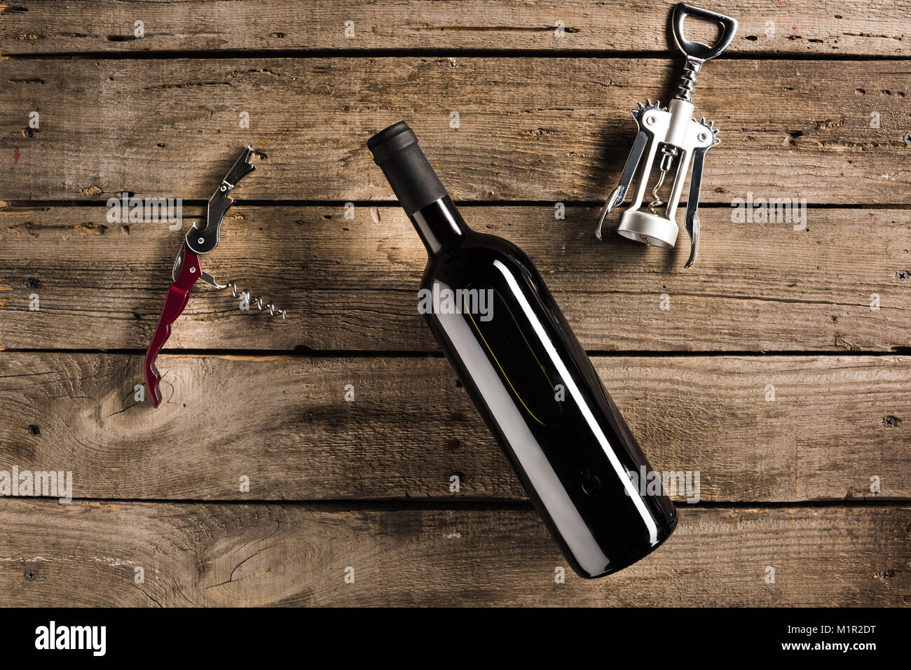 bottle of red wine and corkscrews - Stock Image