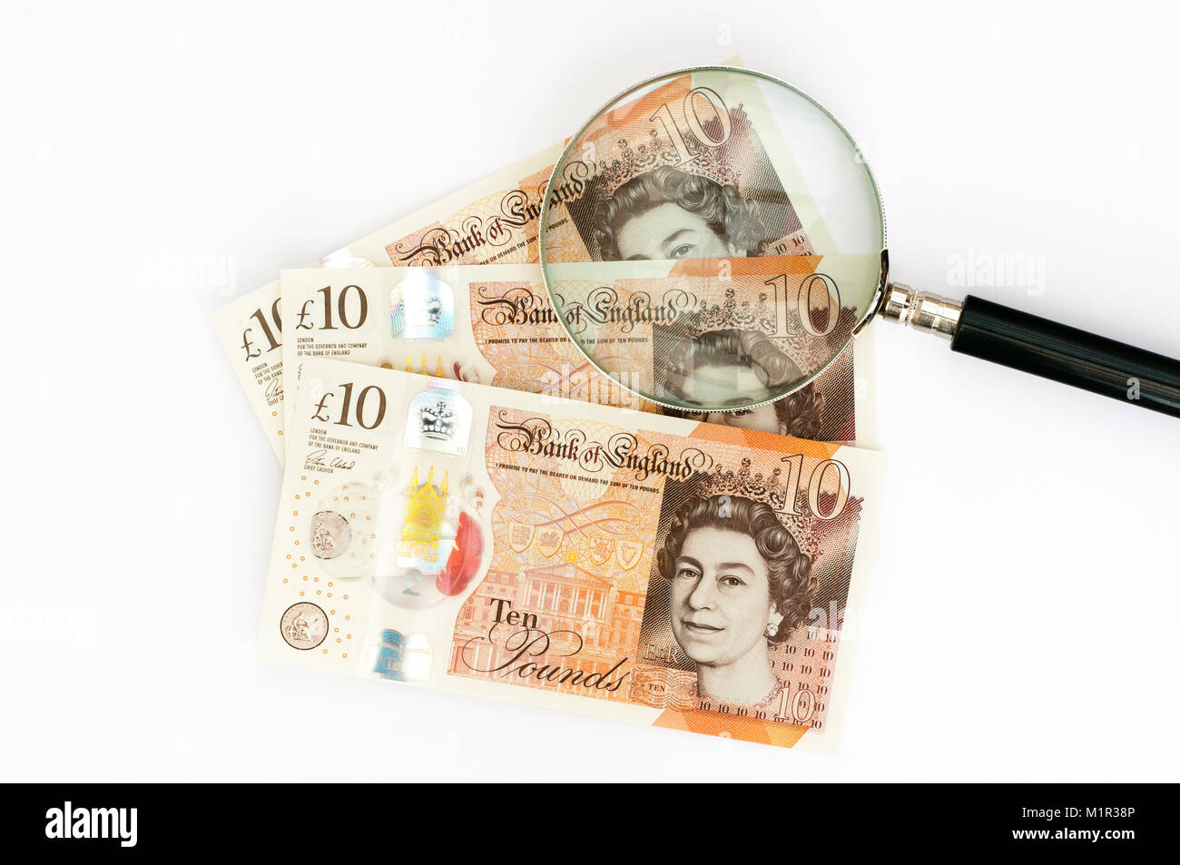 UK United Kingdom Polymer Ten 10 Pound Bank Notes under a magnifying glass - Stock Image