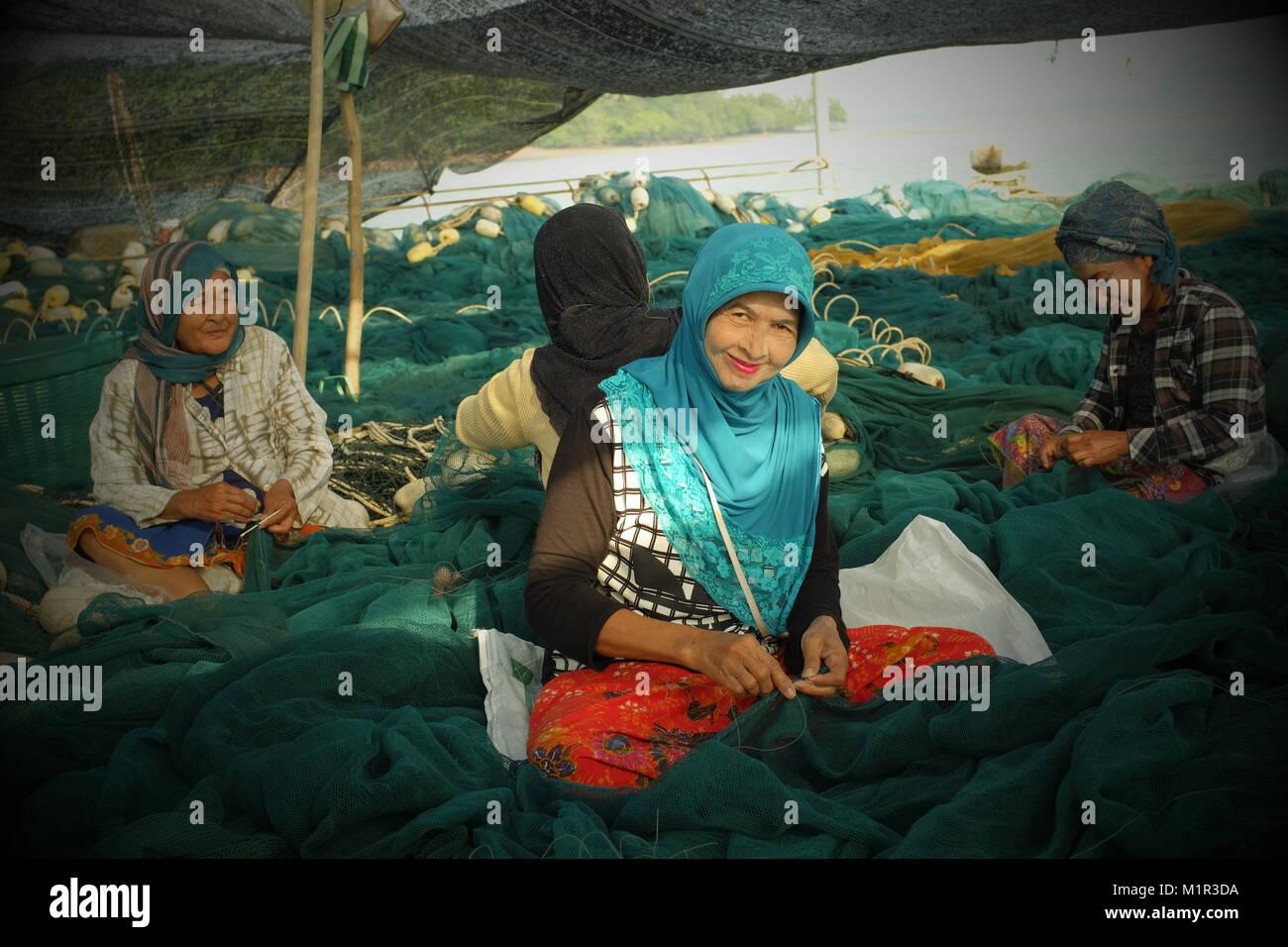 Local Muslim women weave the fishing net in koh Yao Yai, a Thai island in the Andaman Sea. 20-Jan-2018 - Stock Image