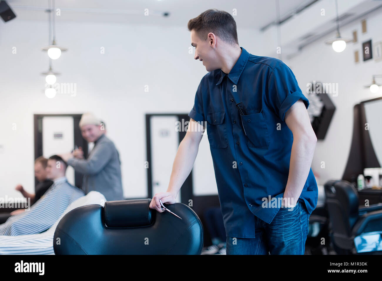 Barber on the chair. Barber expects the client to sit in the chair. - Stock Image