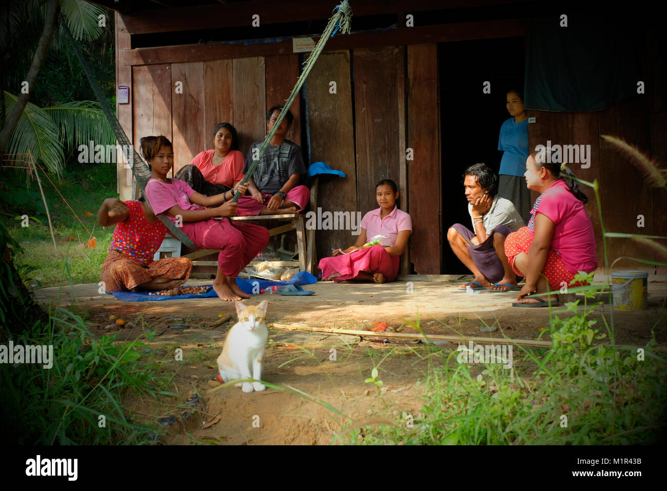 Rubber tapping workers from Burma rest in front of their dwelling place in koh Yao Yai, a Thai island in the Andaman - Stock Image