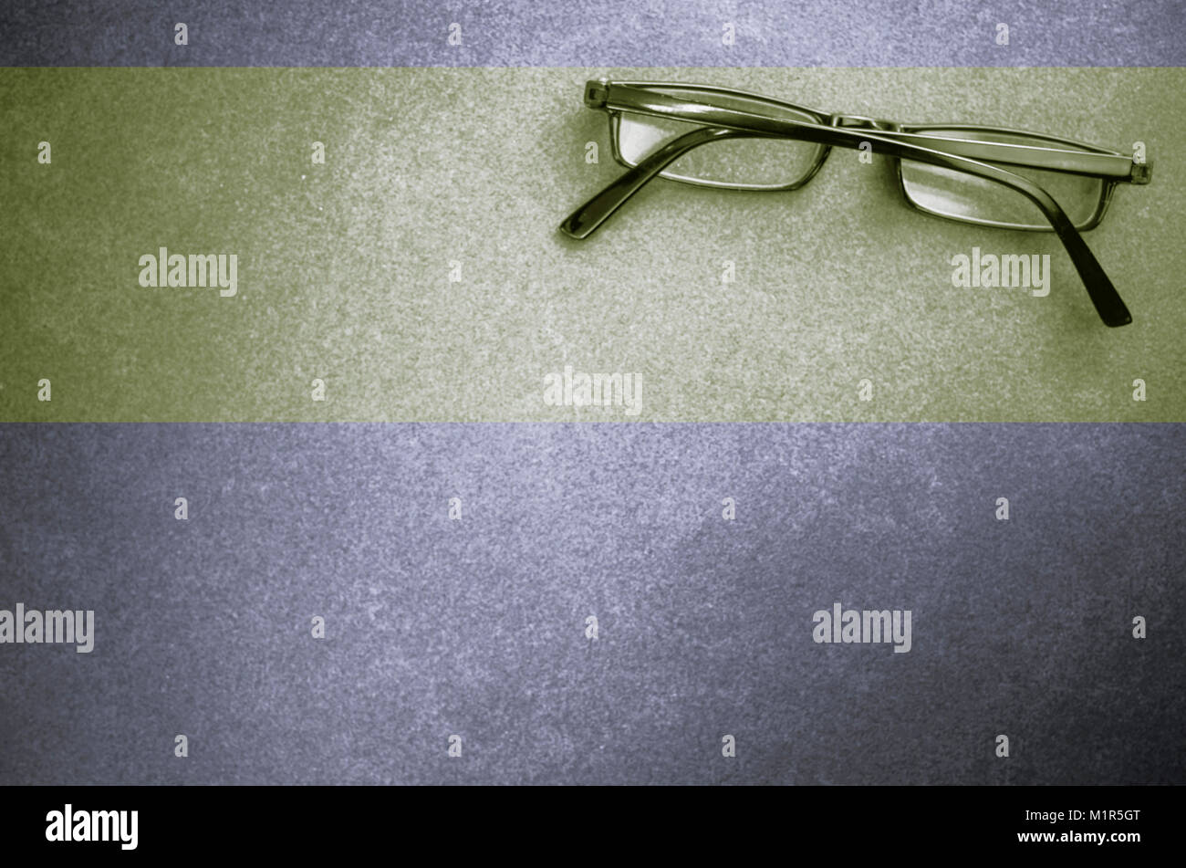 closed eyeglasses on a dark stone surface - top view - Stock Image