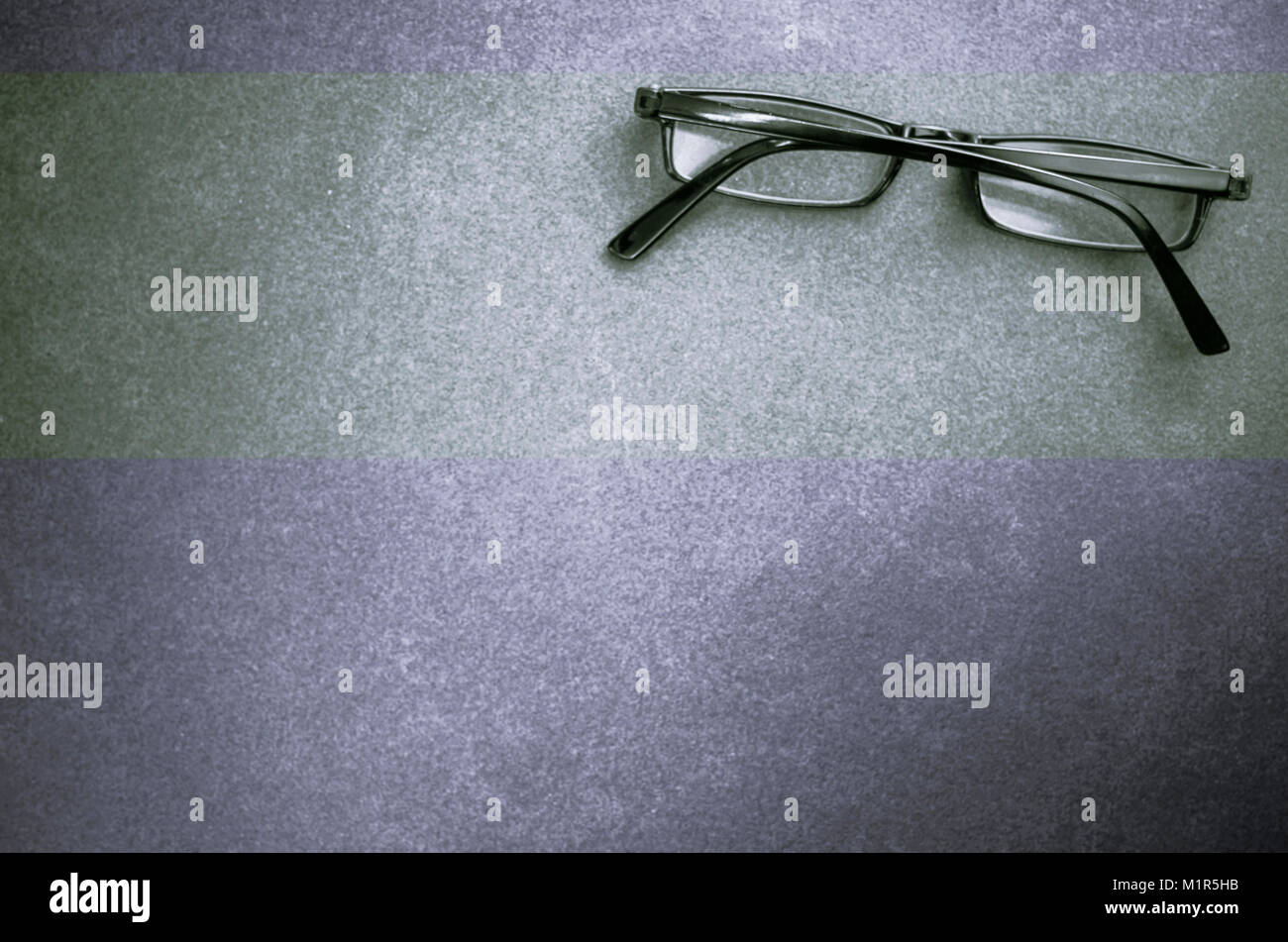 closed eyeglasses on a dark stone surface - top view Stock Photo