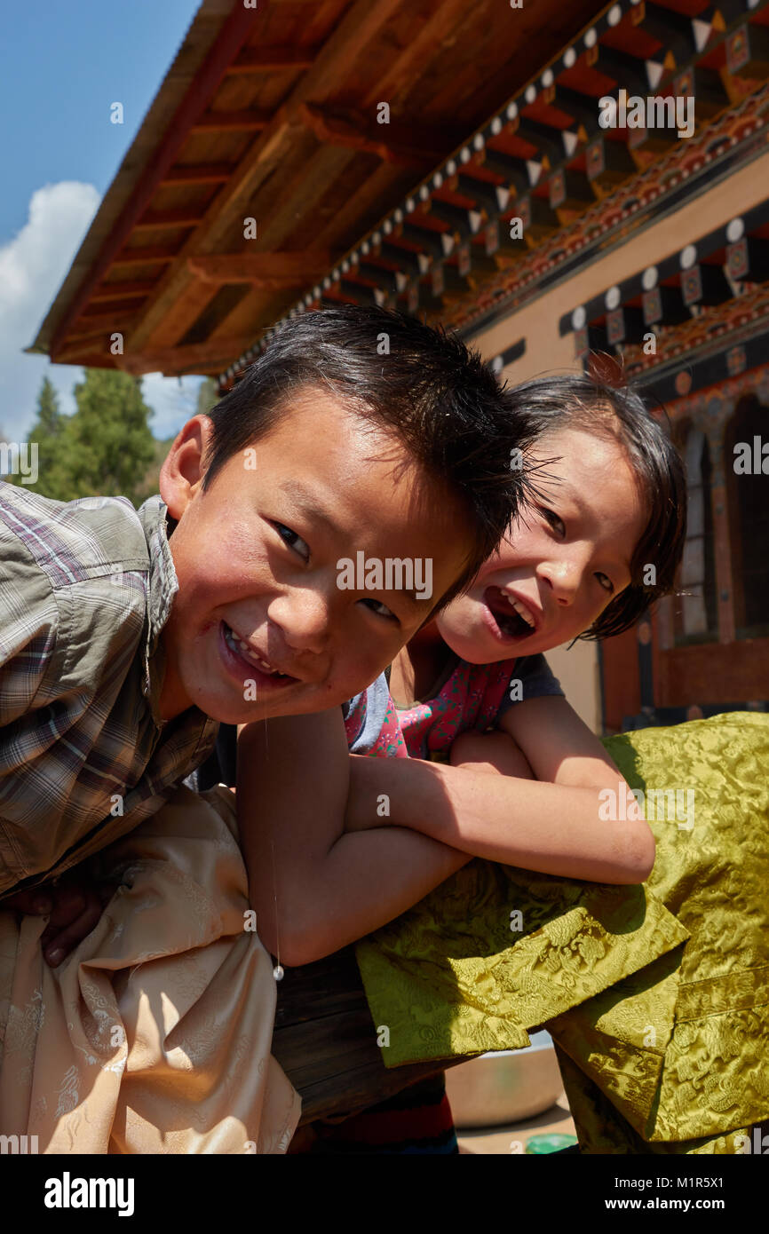 Boy and girl perching on fence of house and smiling in Bhutan - Stock Image
