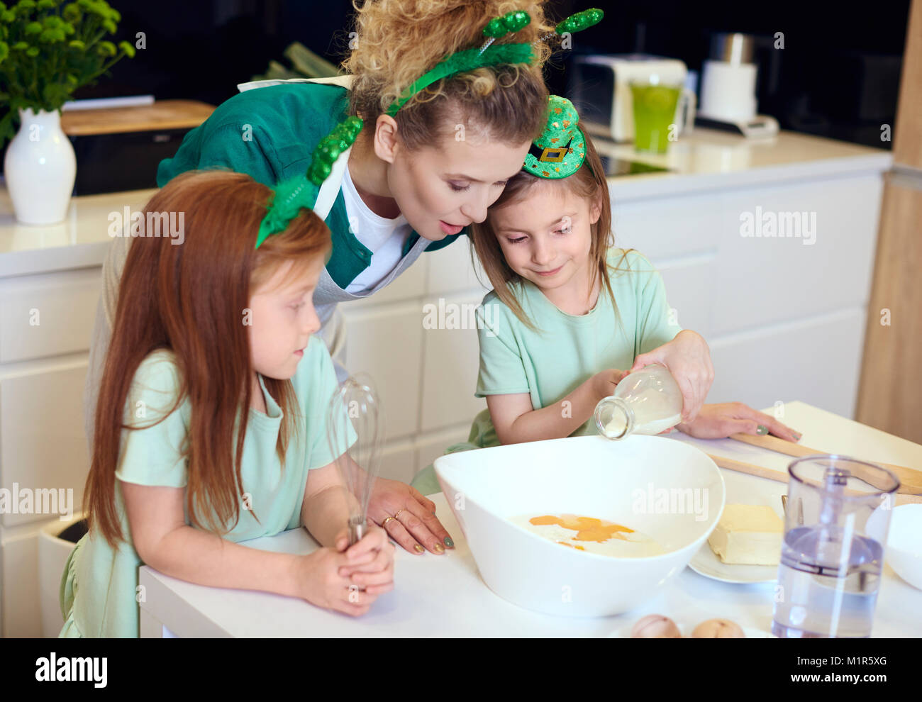 Mother teaching her children how to bake cupcake - Stock Image