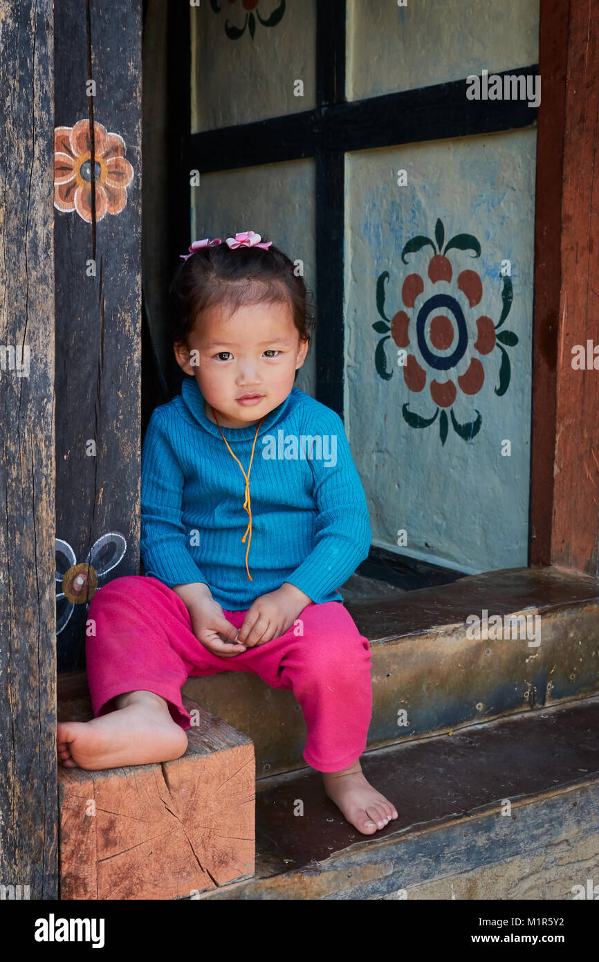 Young little girl sitting at doorway of house wearing blue top and pink bottoms in Bhutan - Stock Image