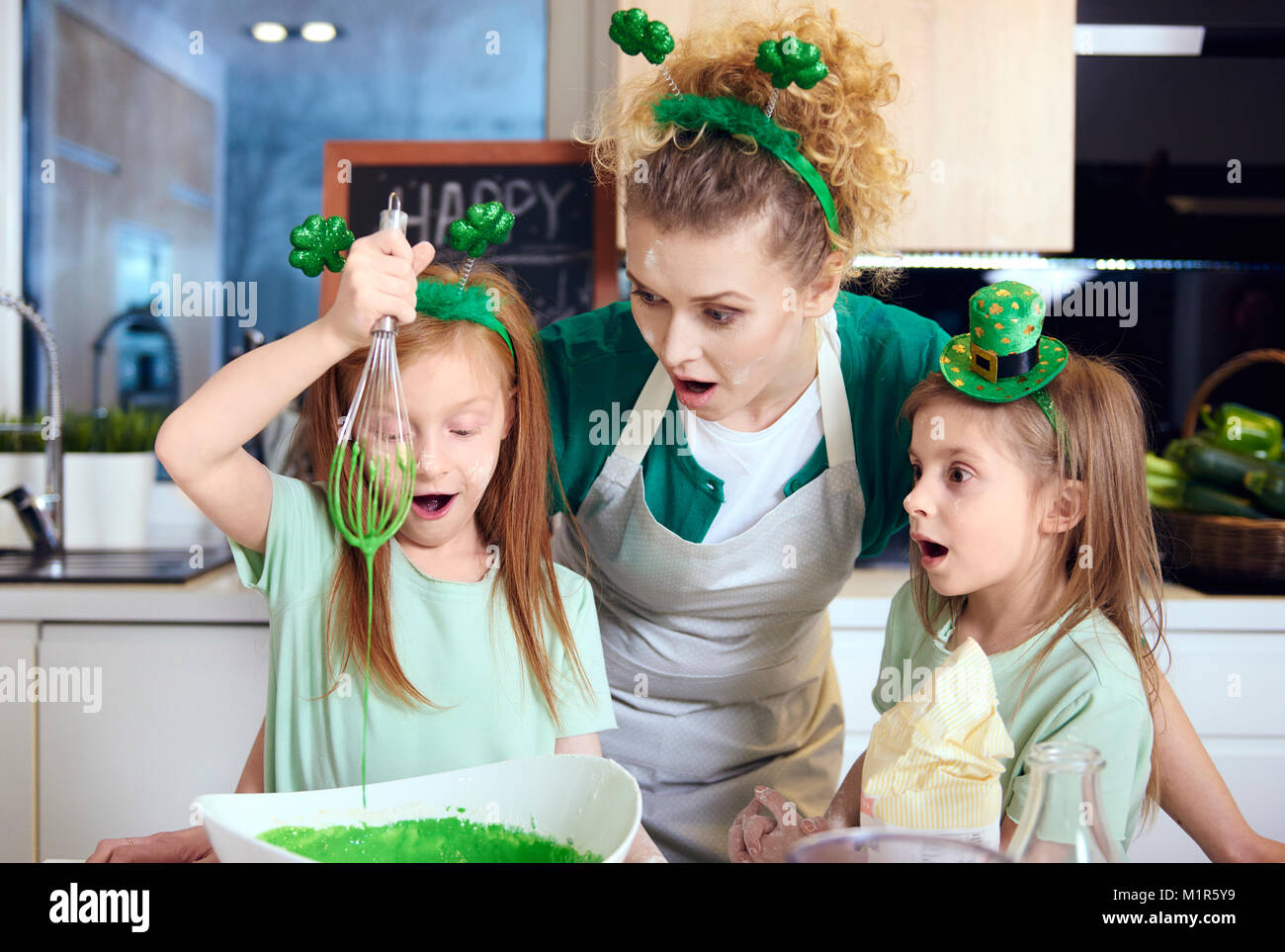 Shocked mother with daughters mixing fondant icing - Stock Image