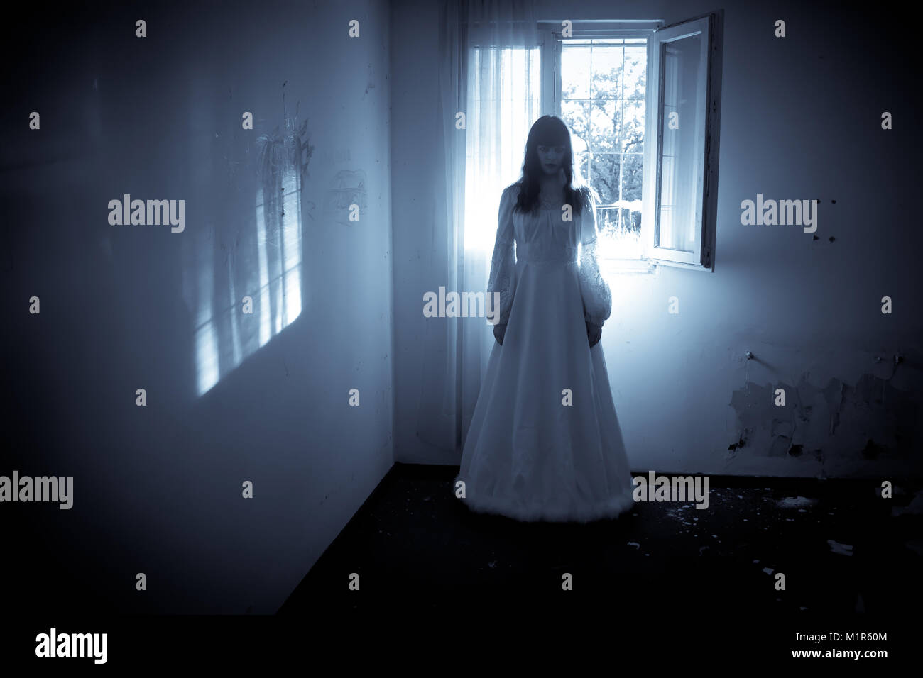 Horror Scene of a Creepy Woman in the Wedding Dress - Stock Image