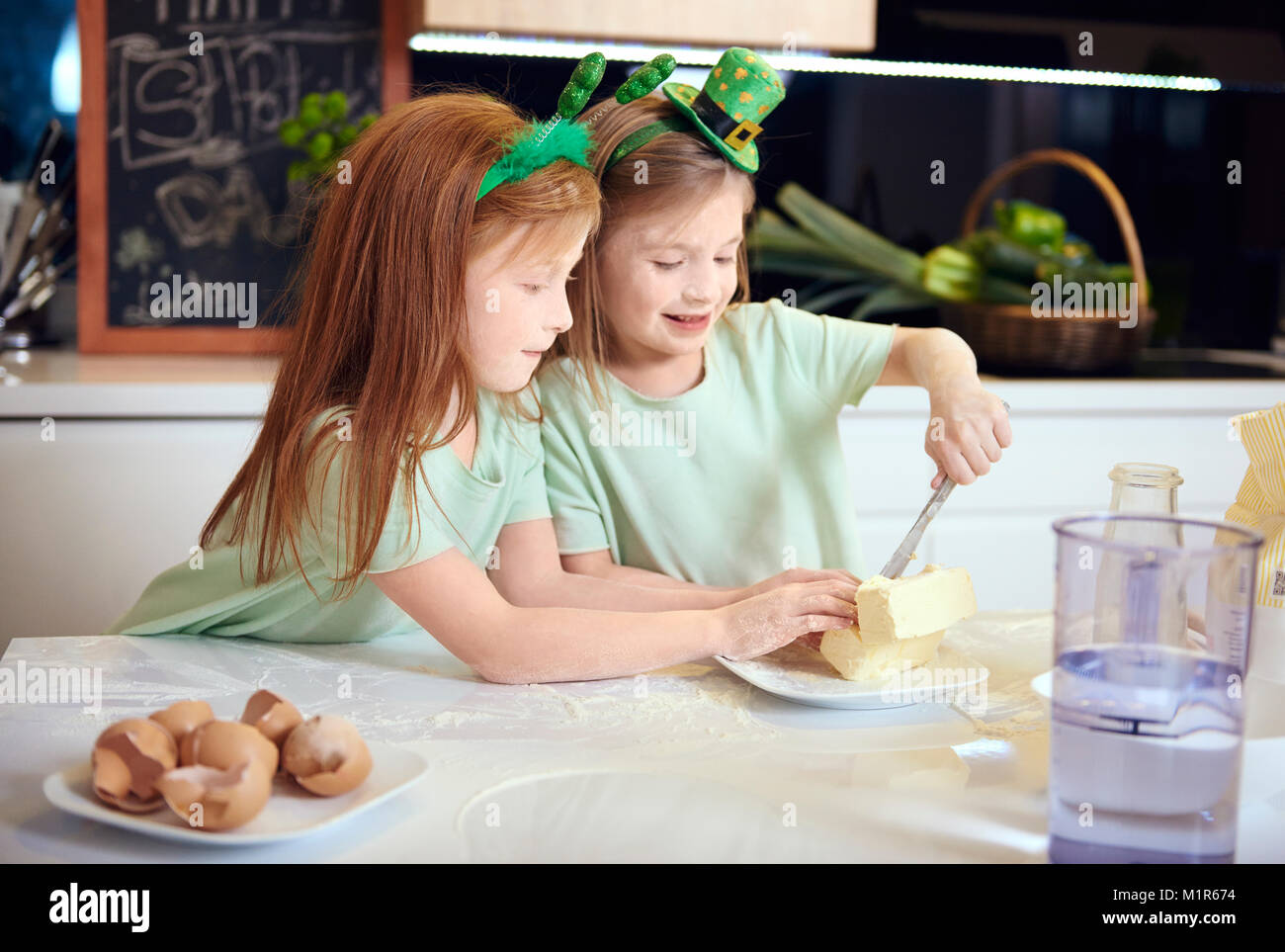 Cheerful siblings baking cookie together - Stock Image