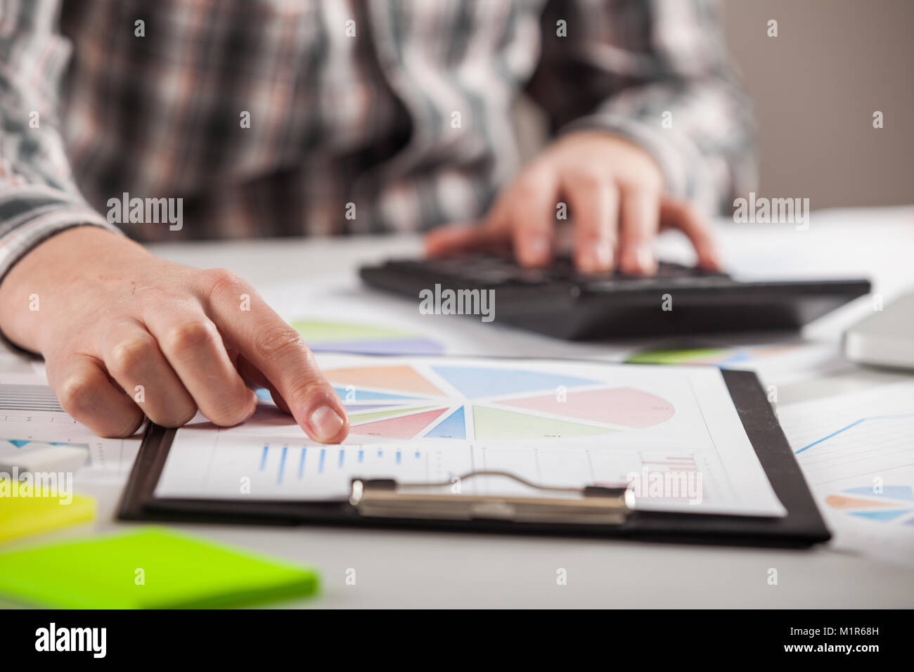 Businessman working with graph documents. Stock market chart and finger pointing on tablet in office. - Stock Image