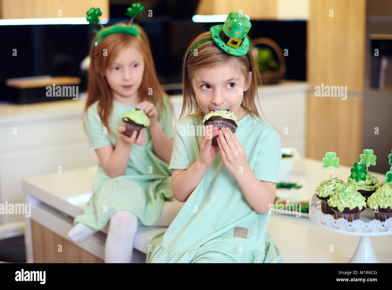 Portrait of children eating cupcake - Stock Image