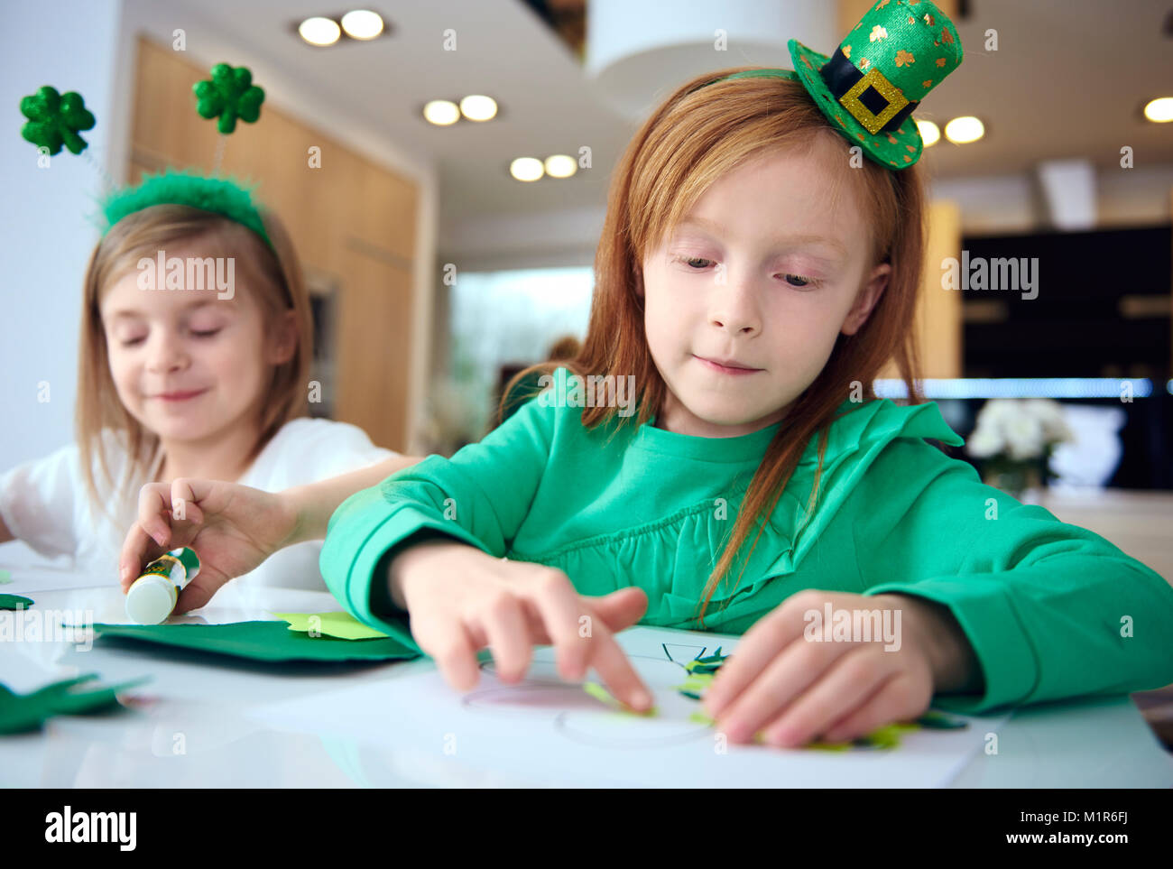 Portrait of siblings making ornament at irish party - Stock Image