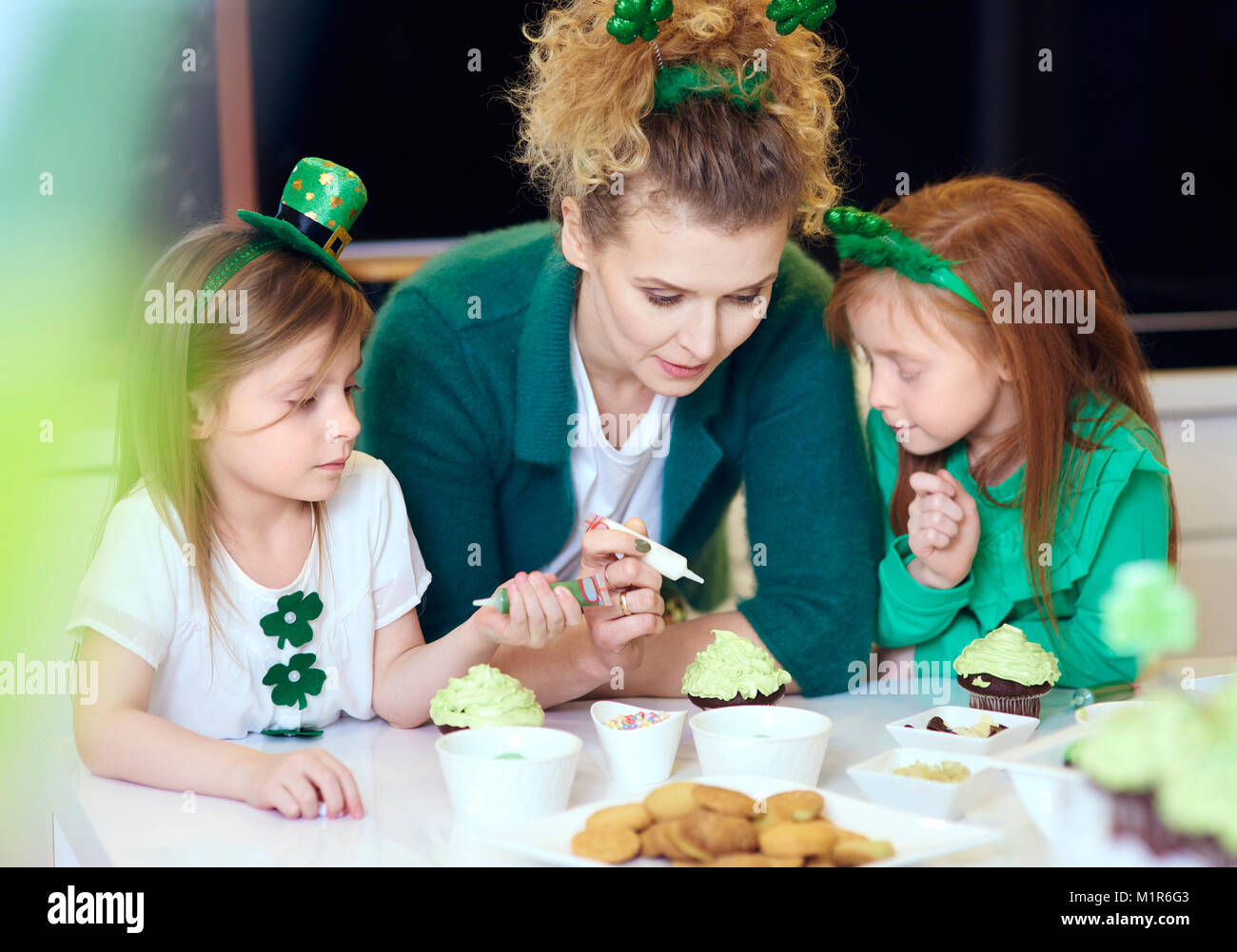 Interested children decorating cupcakes with mother - Stock Image