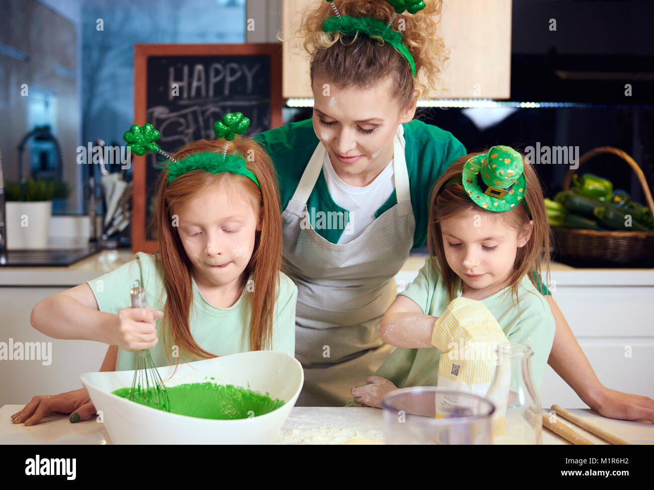 Children mixing fondant icing under mother's supervision - Stock Image